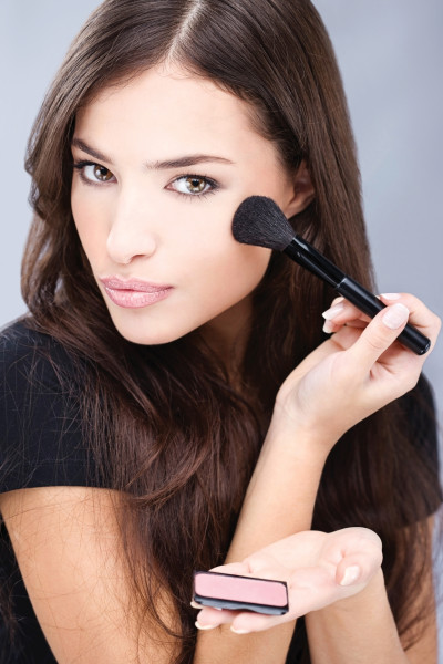 young pretty girl doing makeup with powder brush