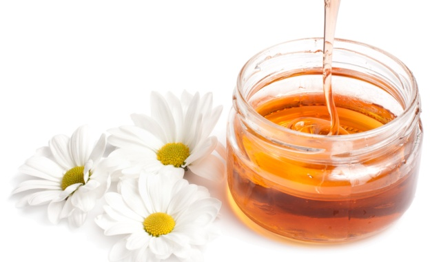 Jar of honey and three daisies. isolated