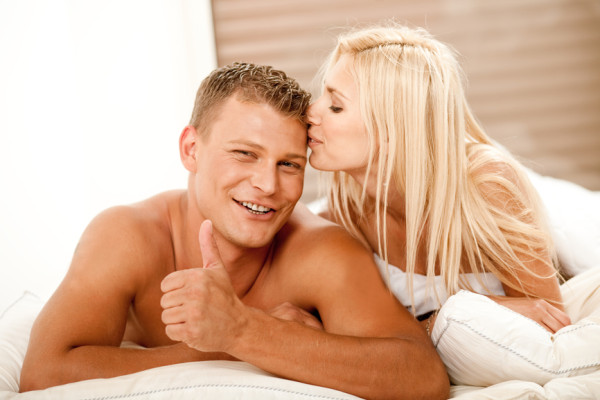 Young man showing thumbs up as woman kisses him on head