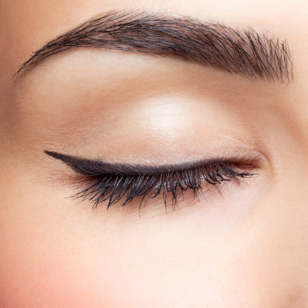 close-up portrait of young beautiful woman's closed, eye zone make up with black arrow