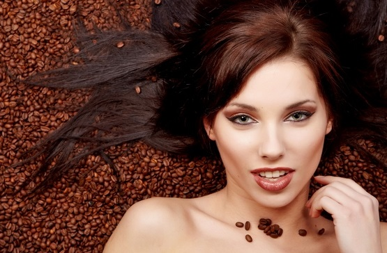 A beautiful young  woman in a bed of brown silk sheets