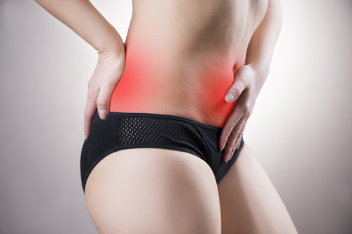 Woman with abdominal and back pain. Pain in the human body on a gray background with red dot