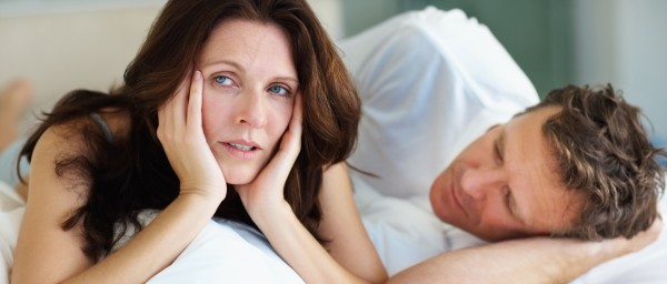 Sexual related problems - Female lying on bed beside her husband in deep thought