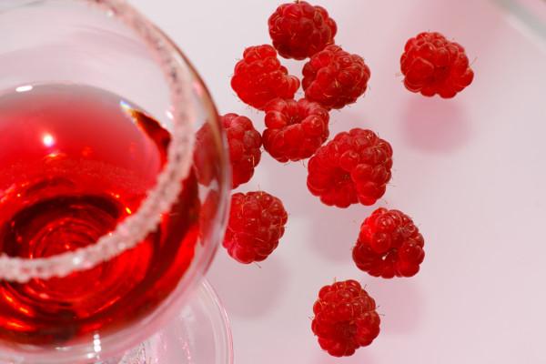 The glass of transparent liquor and raspberry