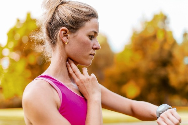 Portrait of an athlete using her watch to mesure her pulse while running in nature