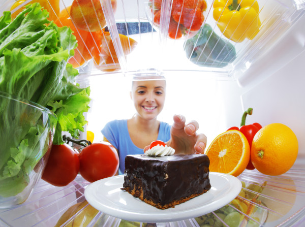 Young woman stops her diet and look for a cake in the refrigerator