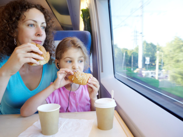 Mother and daughter eat and drink, sitting in armchair at table near window of moving speed train