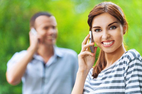 portrait young beautiful happy couple talking phone