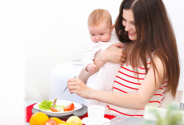 Mother and Baby eating at Home. Happy Smiling Family Portrait