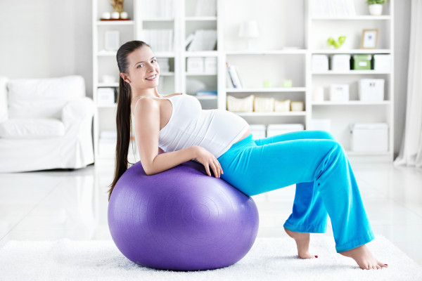 A pregnant young woman is doing on fitball