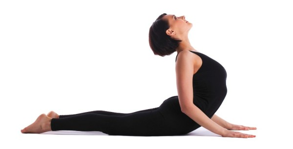 young woman training in yoga asana - cobra bhujangasana pose