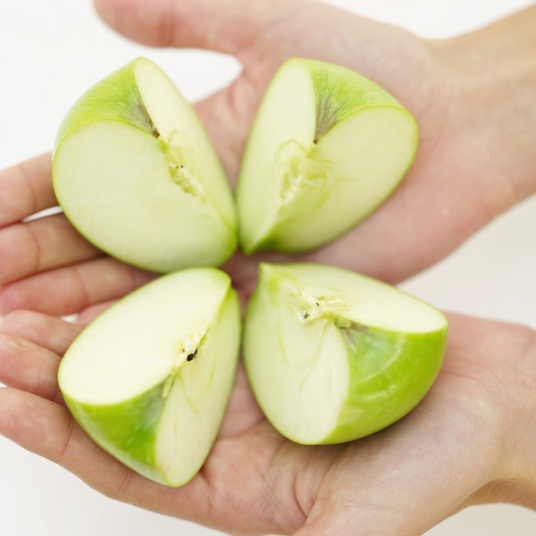 high angle view of a person's hand holding slices of green apple