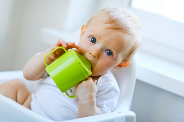 Lovely baby  sitting in chair and drinking from cup