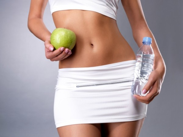 Healthy female body with apple and water