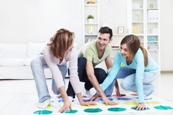 Young happy people playing twister at home
